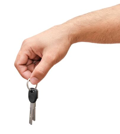 Male hand holding keys isolated on a white photo