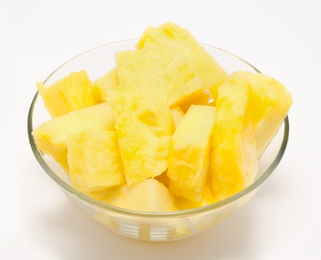 Pineapple chunks in the bowl isolated on white