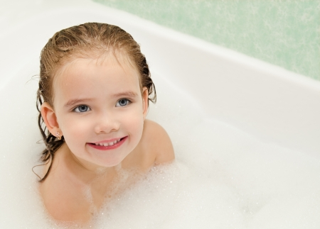 Smiling little girl is taking a bath  photo