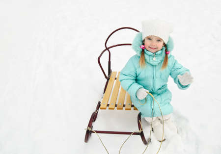 Cute little girl sitting on her sledge in winter day Stock Photo - 16881555