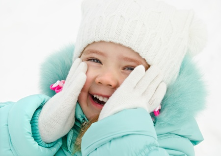Outdoor portrait of cute laughing little girl closing her cheeks in winter day Stock Photo