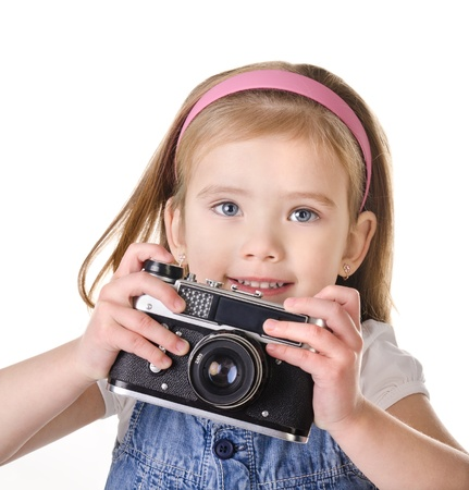 Smiling little girl with old camera isolated on white photo
