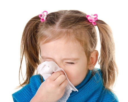 cold and flu: Little girl blowing her nose in a great effort closeup isolated on white