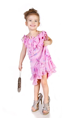 Cute little girl in big shoes and dress isolated on white background  photo