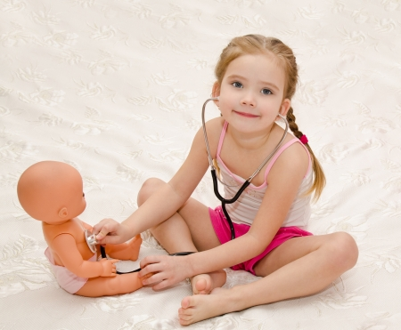 role playing: Smiling little girl playing with doll in the hospital