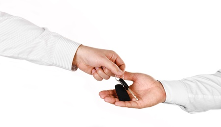 Male hand holding a car key and handing it over to another person isolated Stock Photo - 17660683