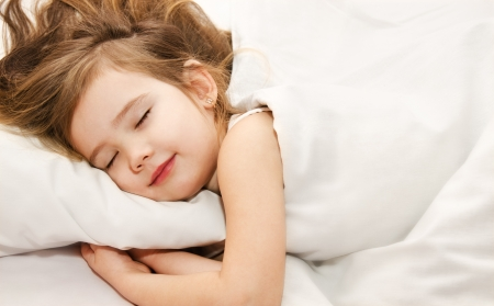 little girl smiling: Adorable little girl sleep in the bed