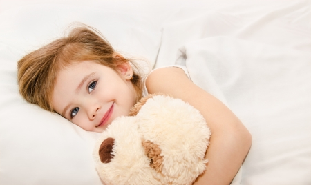 Adorable little girl in the bed with her toy  Stock Photo