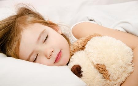 enfant qui dort: Adorable petite fille dormant dans le lit avec son jouet Banque d'images