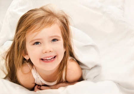 sleeping girl: Adorable little girl awaked up in her bed