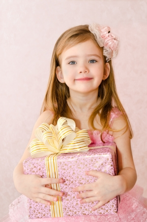 Portrait of cute little girl with gift box photo