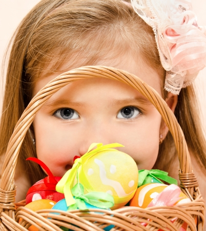 Cute little girl with basket full of colorful easter eggs  Stock Photo