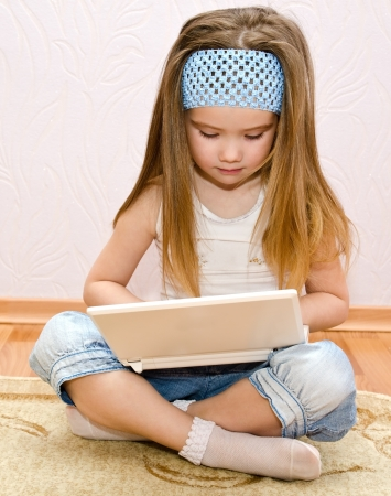Cute little girl with a laptop at home on the floor