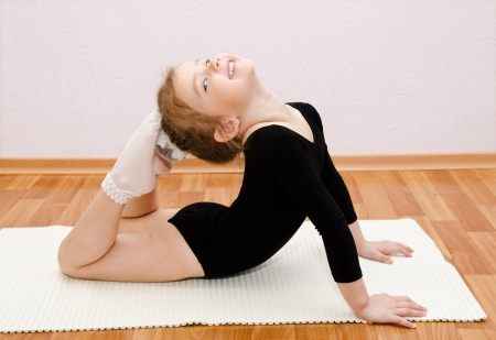 Gymnast smiling little girl doing exercises at home Stock Photo