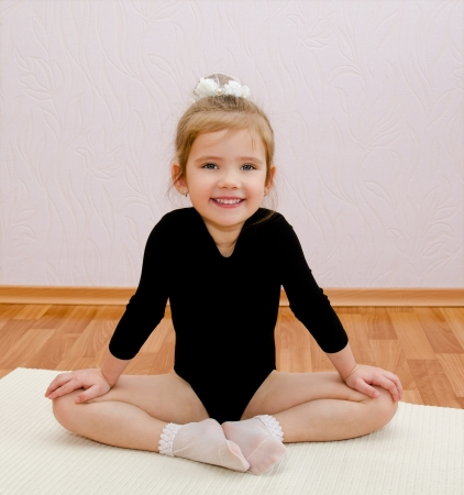 Gymnast smiling little girl doing exercises at home Imagens