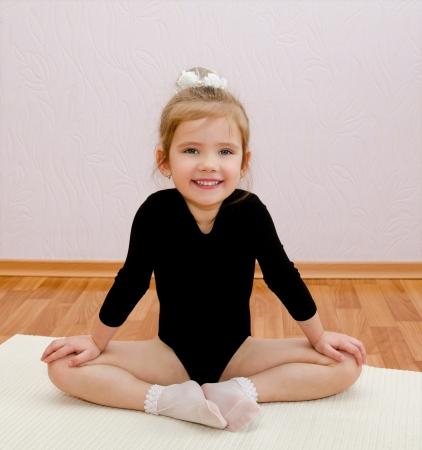 Gymnast smiling little girl doing exercises at home 免版税图像