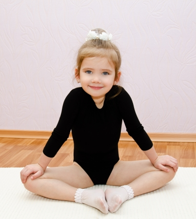 Gymnast cute little girl doing exercises at home Stock Photo