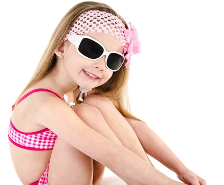 little girl sitting: Cute smiling little girl in swimsuit and sunglasses isolated on white background