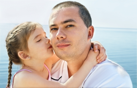 Cute little girl kissing her father on beach vacation photo
