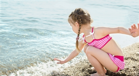 Adorable little girl having fun on beach vacation  photo