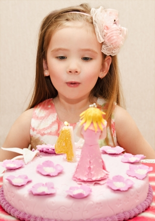 Portrait of cute little girl and her birthday cake photo