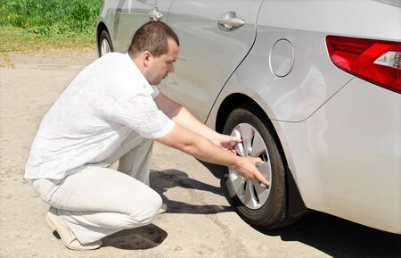 puncture: Car wheel defect man change puncture tire outdoors Stock Photo
