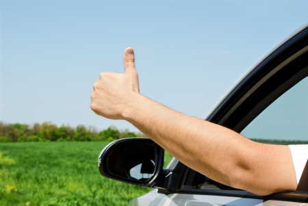 Man inside car showing thumb up outdoor