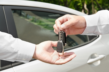 Man handing another person automobile keys new car outdoors