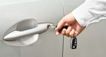 Male hand with key opening car door outdoors photo