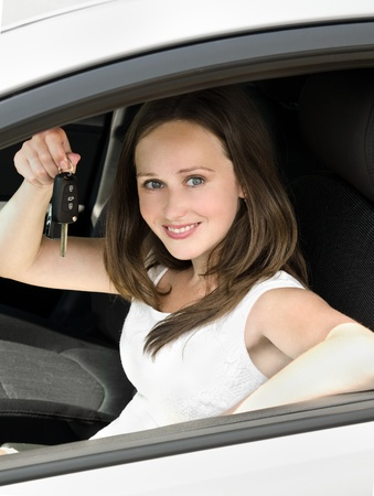 Portrait of young smiling woman holding key in his own car outdoors photo