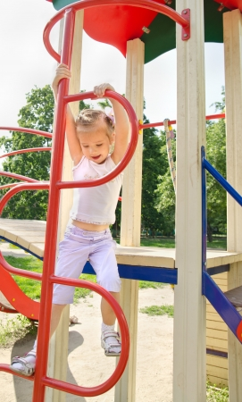 Happy smiling little girl on outdoor playground equipment  photo