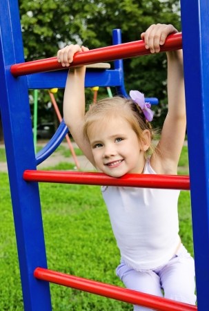 Happy smiling little girl on outdoor playground equipment