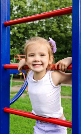 Happy little girl on outdoor playground equipment  photo