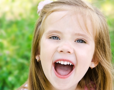 Portrait of screaming little girl in a meadow outdoor photo