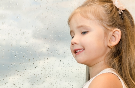 Cute little girl looking out the window on a rainy day  photo