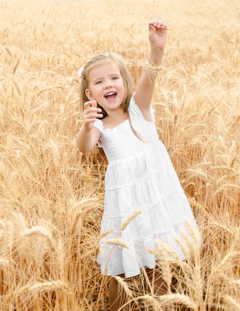 Adorable smiling little girl in the wheat field on summer day  photo