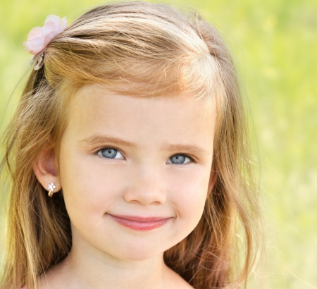 Outdoor portrait of adorable smiling little girl in summer day Stock Photo