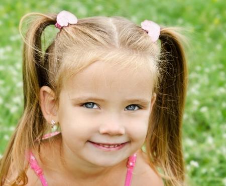 Linda niña sonriente en el prado en día de verano Foto de archivo
