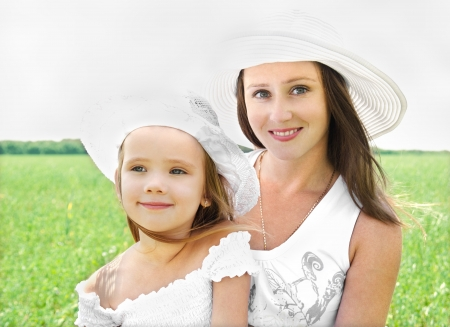 Outdoor portrait of happy smiling young woman and little girl in summer day photo