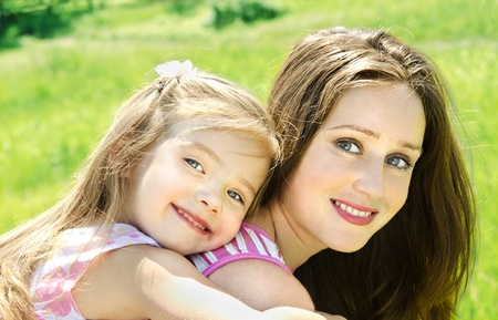 Portrait of smiling beautiful young woman and her little daughter outdoor photo