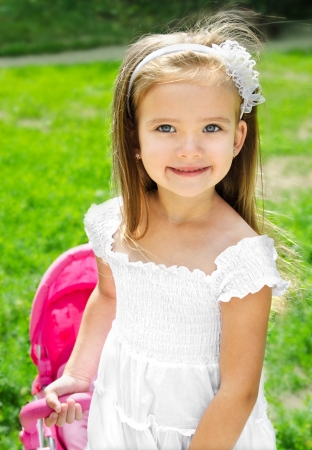 smiling girls: Cute little girl with her toy carriage and doll outdoors