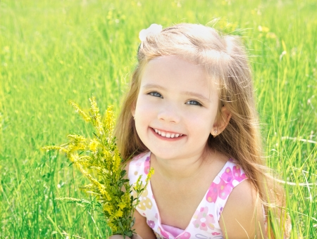 Leuk meisje op de weide met bloemen in de zomer dag