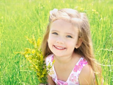Niña linda en el prado con flores en día de verano Foto de archivo