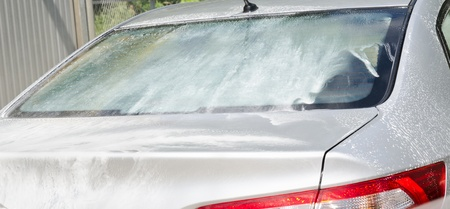 pressured: Manual car washing cleaning with foam and pressured water at service station outdoor Stock Photo