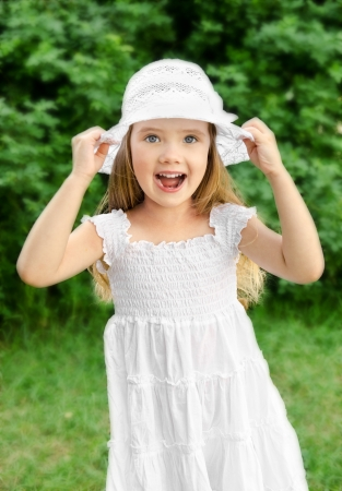 Outdoor portrait of adorable screaming little girl in white dress and hat photo
