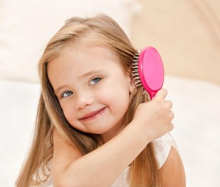 Retrato de la niña sonriente cepillarse el pelo primer
