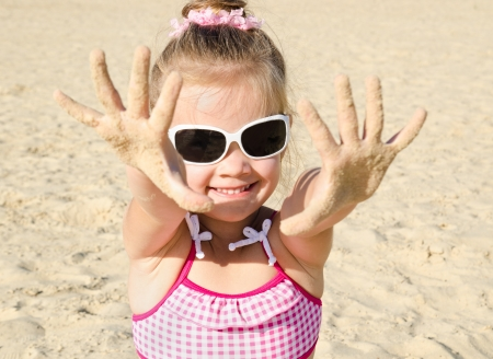 Cute smiling little girl playing on beach photo