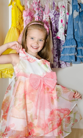 Cute smiling little girl measures a dress from the wardrobe  photo