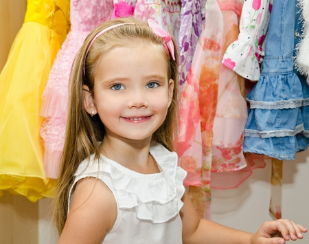 Cute smiling little girl chooses a dress from the wardrobe  photo