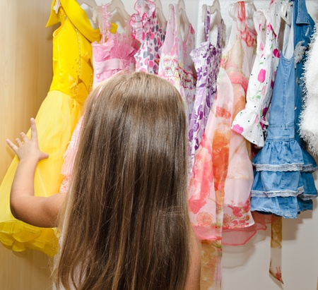 Little girl chooses a dress from the wardrobe  photo